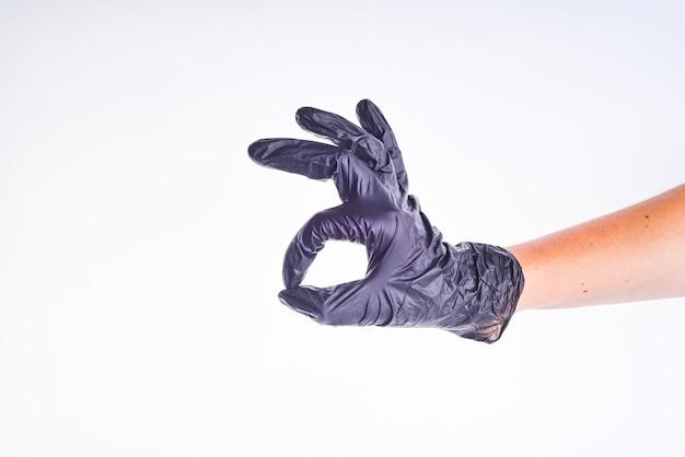 Dien zwarte handschoen in toont ok gebaar. de hand van de dokter geeft het oké teken. kopieer ruimte.