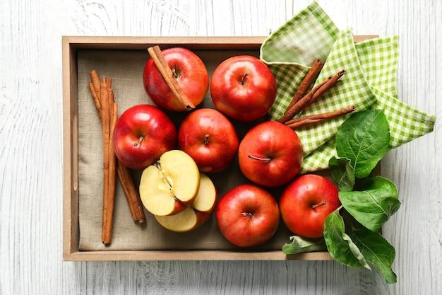 Dienblad met appels en kaneelstokjes op houten oppervlak