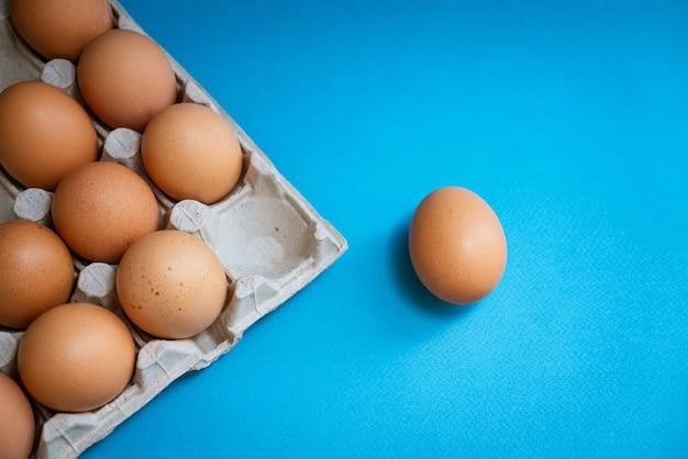 Dienblad met bruine eieren op een blauwe achtergrond, één ei is afzonderlijk