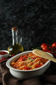 Dienblad met deegwaren met tomatensaus tegen zwarte smokey geïsoleerde achtergrond