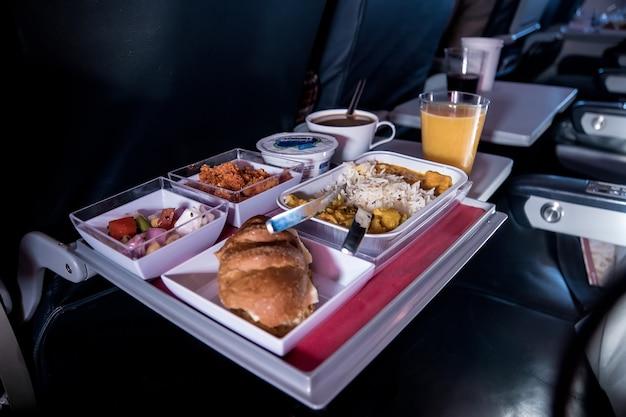 Dienblad met eten. de passagier eet voedsel aan boord van het vliegtuig op de achtergrond van het raam. maaltijden in het vliegtuig. verschillende sets eten op de klaptafel.
