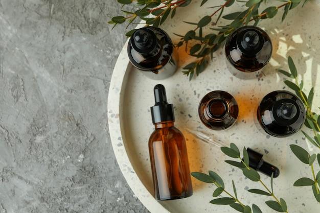Dienblad met flessen eucalyptusolie en takken op grijze lijst