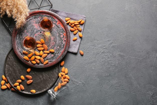 Dienblad met glazen amandellikeur en noten op donkere tafel met kopieerruimte