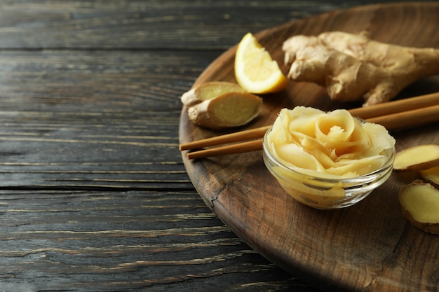 Dienblad met ingemaakte gember, eetstokjes en gember op houten lijst