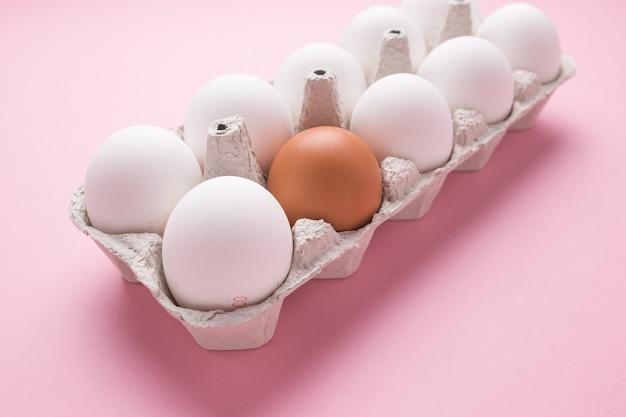 Dienblad met kippeneieren op een roze achtergrond. een bruin ei onder wit. het concept van individualiteit.