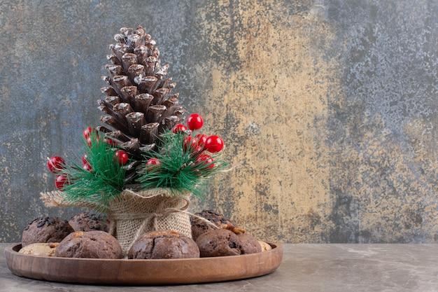 Dienblad met koekjes met in het midden een decoratieve dennenappel op marmer.