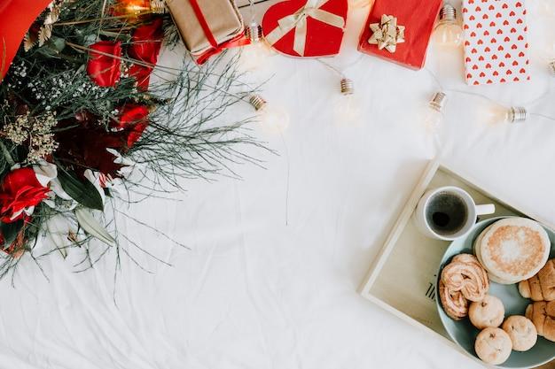 Dienblad met ontbijt dichtbij boeket en cadeaus