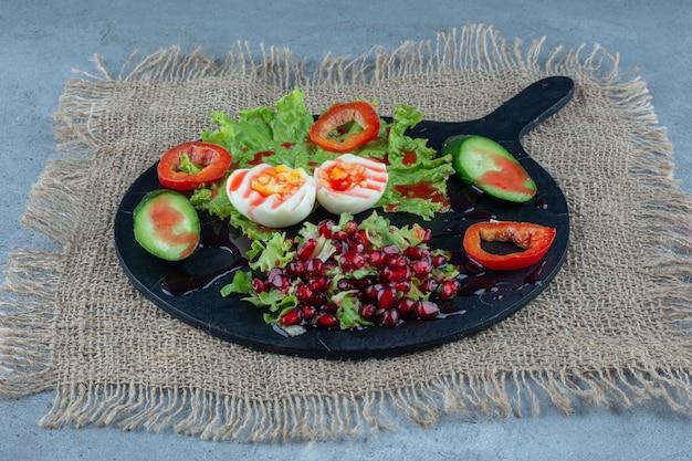 Dienblad met ontbijt gemaakt van gekookte eieren, plakjes komkommer en paprika en granaatappelsalade op marmer.
