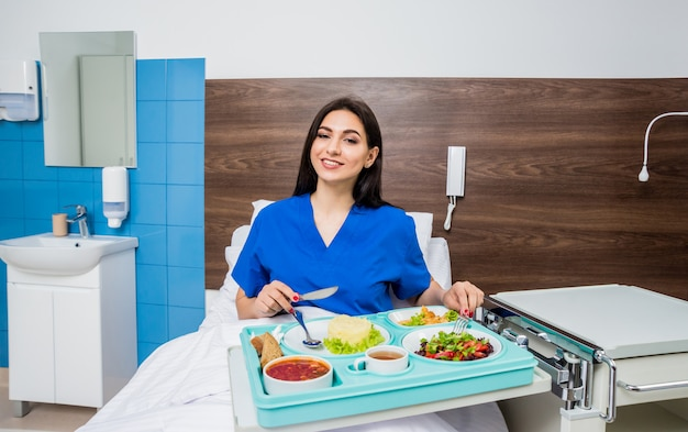 Dienblad met ontbijt voor de jonge vrouwelijke patiënt. de jonge vrouw die in het ziekenhuis eet.