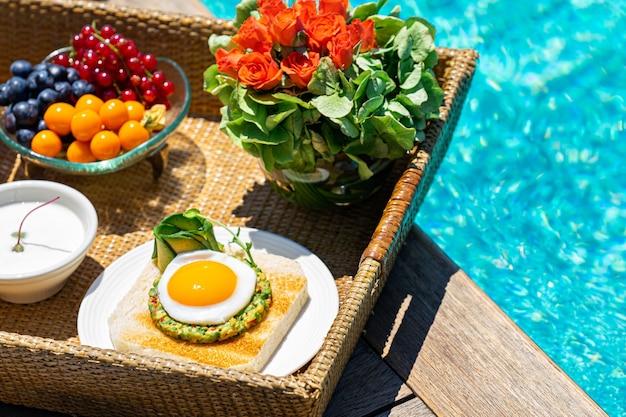 Dienblad met ontbijtvoedsel bij het zwembad
