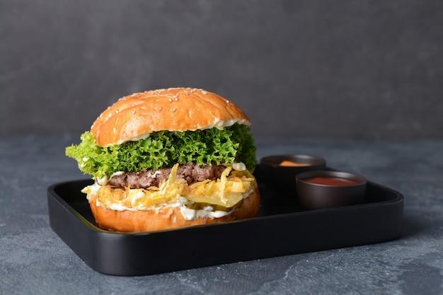 Dienblad met smakelijke hamburger en sauzen op donkere ondergrond