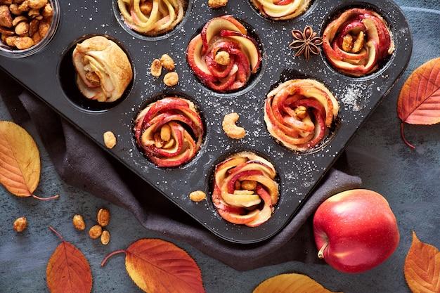 Dienblad van appelrozen die in bladerdeeg op grijze geweven achtergrond worden gebakken