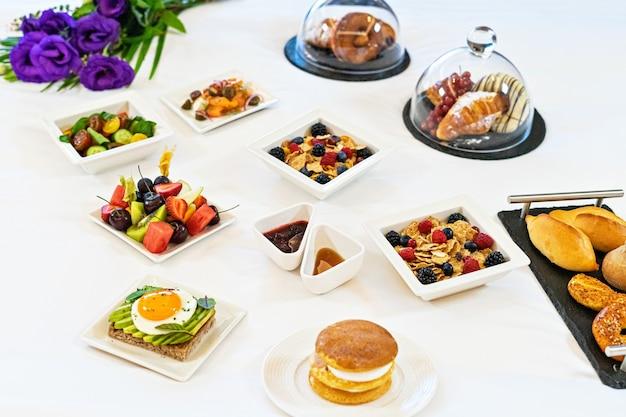 Dienbladplaten met ontbijtmaaltijd op een bed in een hotel