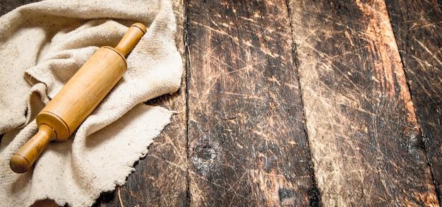 Dienende achtergrond. deegroller de oude stof. op een houten tafel.