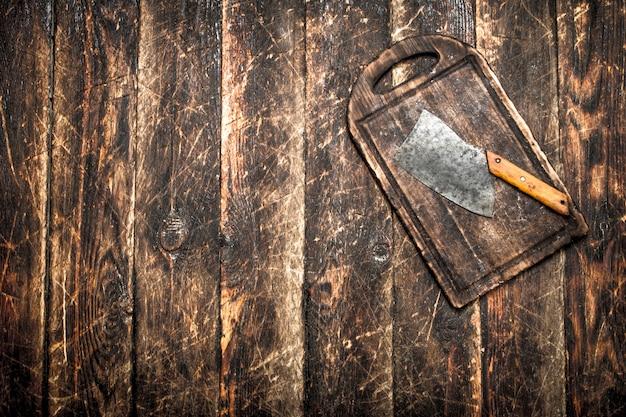 Dienende achtergrond. oude bijl op een snijplank. op een houten tafel.