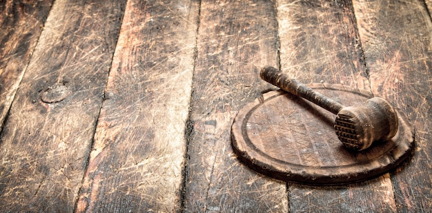 Dienende achtergrond. oude vleeshamer op een snijplank.