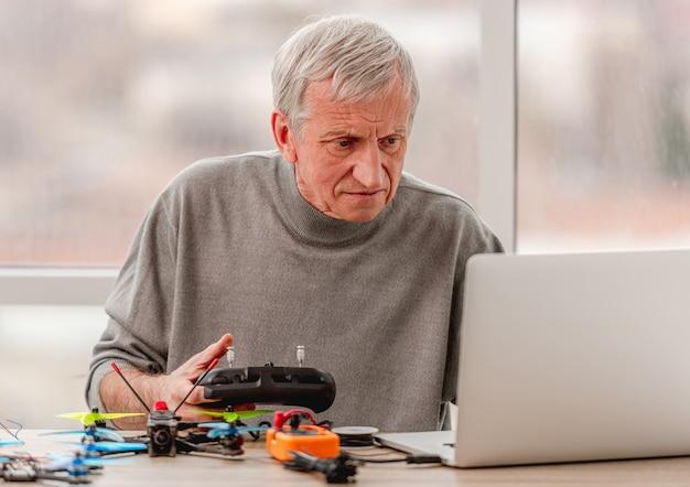 Dienst man kijken naar laptop en quadcopter bedieningspaneel programmeren