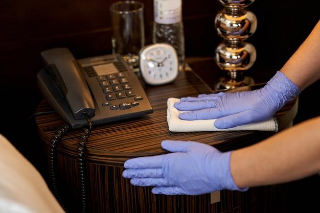 Dienstmeisje doet desinfectie van oppervlakken in hotelkamer