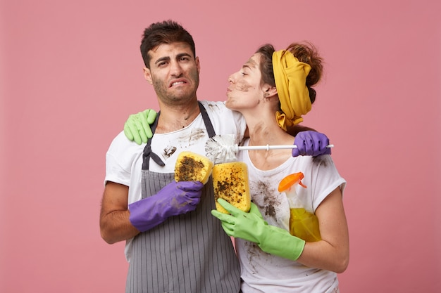 Dienstmeisje in vrijetijdskleding en beschermende handschoenen gaat haar man kussen, die er moe en uitgeput uitziet