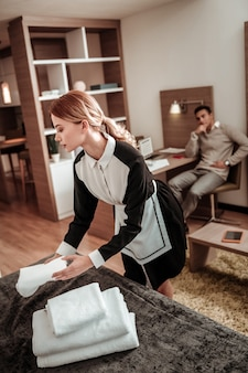 Dienstmeisje met paardenstaart. hardwerkende professionele hotelmeid met mooie paardenstaart die handdoeken op het bed organiseert