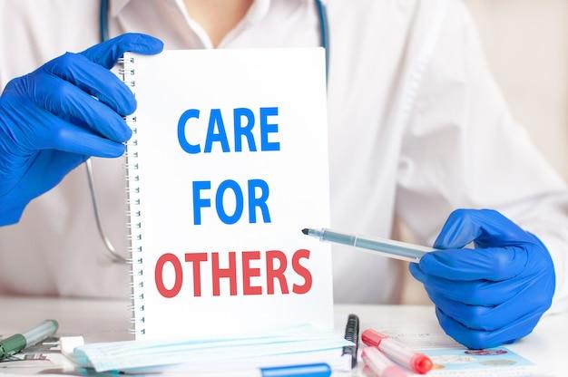 Dient blauwe handschoen met een vel papier in. een vel papier met de tekst zorg voor anderen