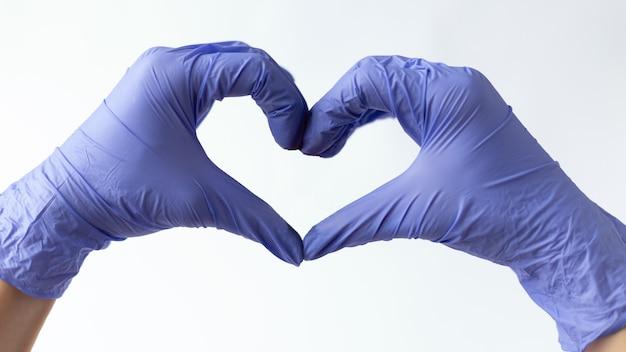 Dient medische handschoenen in toont een hart.