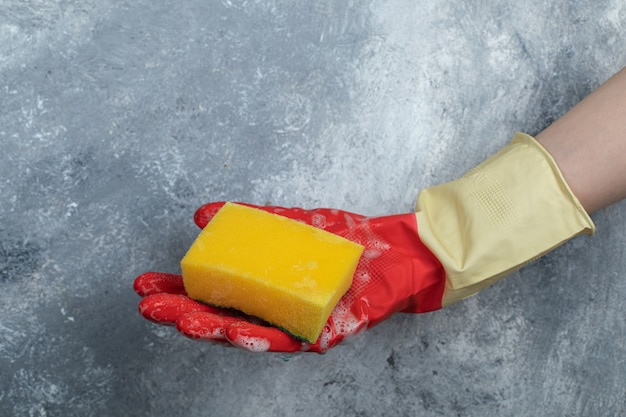 Dient rode beschermende handschoenen in houdend spons.