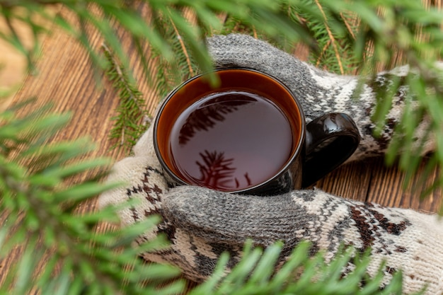 Dient vuisthandschoenen in houdend kop thee dicht omhoog op geborsteld bruin