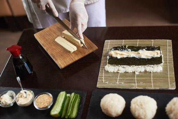 Dient wegwerphandschoenen in die omelet op houten raad snijden