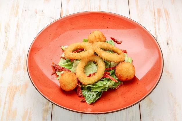 Diep beslag gefrituurde inktvisringen calamares met groene salade