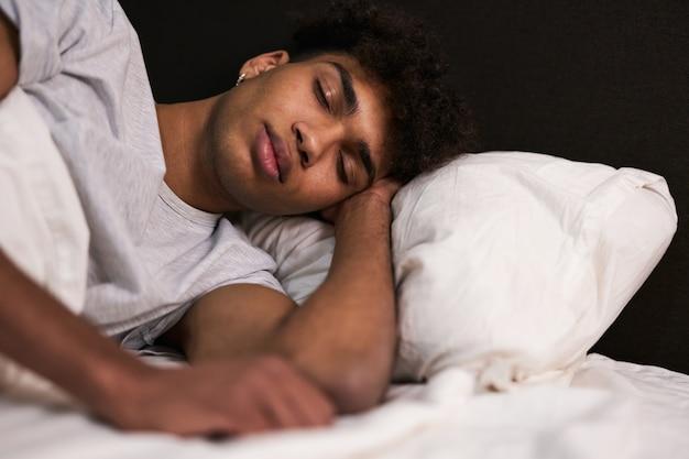 Diep slaapportret van een vreedzame jonge kerel die thuis in zijn knusse bed slaapt
