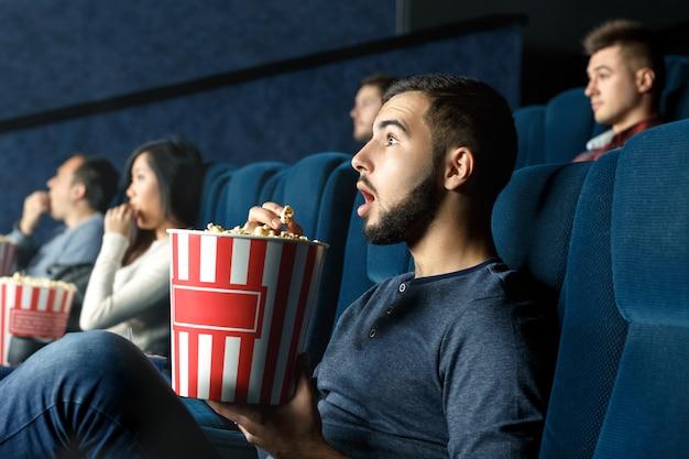 Diep vermaakt. horizontaal portret van een jonge man die aandachtig naar film kijkt met zijn mond open