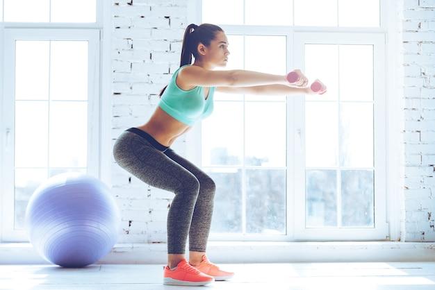 Diepe hurkzit. zijaanzicht van jonge mooie vrouw in sportkleding die squat doet en halters vasthoudt terwijl ze voor het raam in de sportschool staat