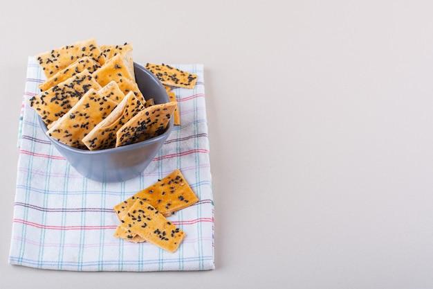 Diepe kom crackers met zwarte zaden op witte achtergrond. hoge kwaliteit foto