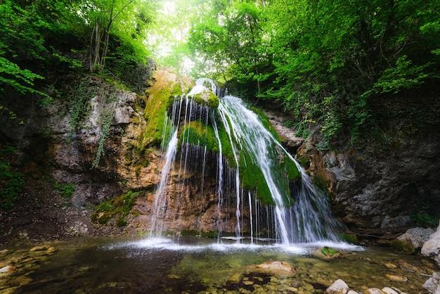 Diepe waterval in grote stralen valt van een klif in een groen bos