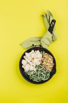 Diepvriesgroenten: snijbonen, bloemkool en een mix van groenten in een zwarte pan op een felgele achtergrond.