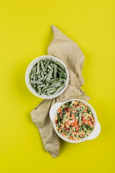 Diepvriesgroenten: snijbonen en een mix van groenten in witte borden met een servet op een felgele achtergrond.