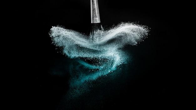 Diepzee poeder kleur splash en zilveren borstel voor make-up artiest