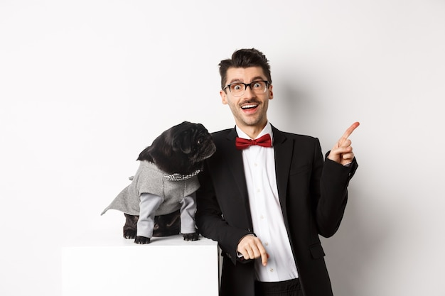Dieren, feest en viering concept. blije en verbaasde jongeman en schattige mopshond in kostuum die op een witte achtergrond staat, hondenbezitter die naar rechts wijst