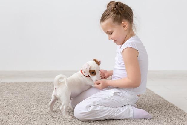 Dieren, kinderen en huisdieren concept - klein kind meisje, zittend op de vloer met schattige puppy en