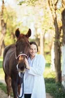 Dierenarts die een paard buiten aait op een ranch.