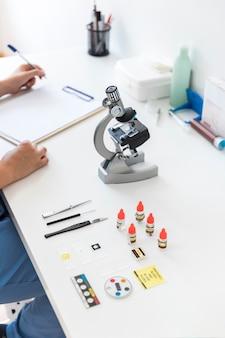 Dierenarts die op klembord met microscoop en medisch materiaal in laboratoriumbureau schrijft