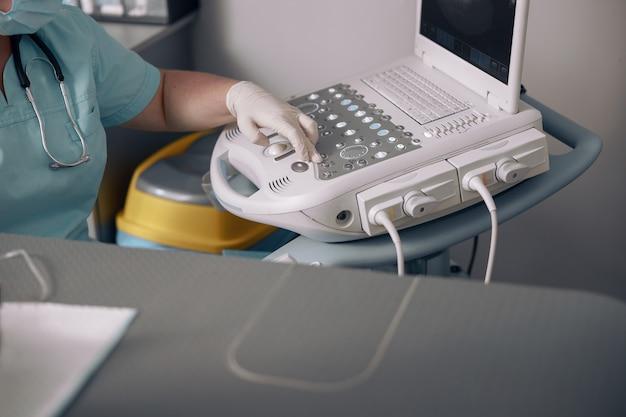 Dierenarts drukt op toets op bedieningspaneel van ultrasone machine bij onderzoek in kliniek