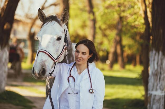 Dierenarts genieten met een paard buiten op ranch.
