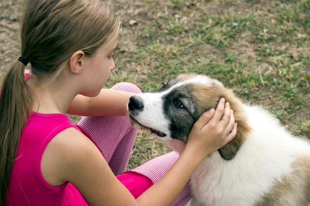 Dierlijke liefde. schattig klein meisje in het veld aait haar lieve hond