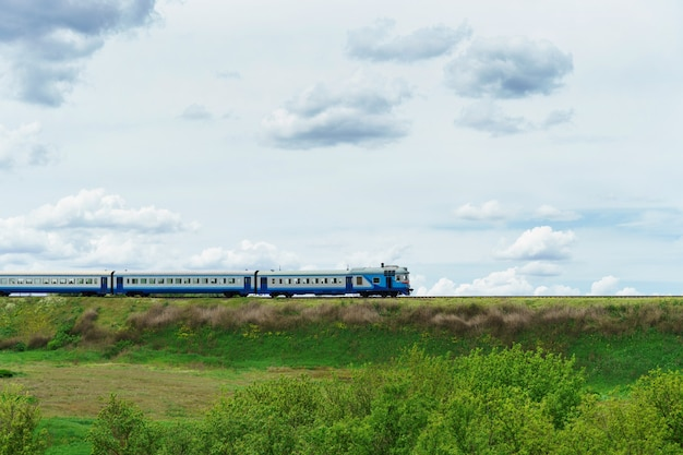 Diesel trein. blauwe passagierstrein rijdt op een spoor in het gras. spoorlijn in het veld.
