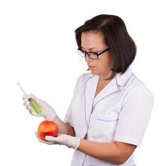 Diëtist wetenschapper vrouwelijke arts houden verse perzik wordt geïnjecteerd met spuit op wit op een witte achtergrond