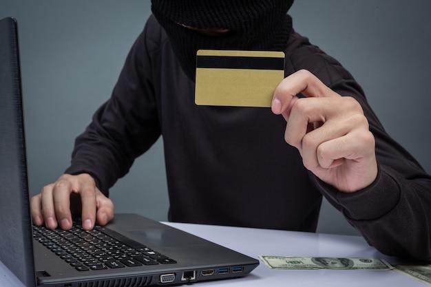 Dieven houden creditcards vast met behulp van een laptop voor het hacken van wachtwoorden.