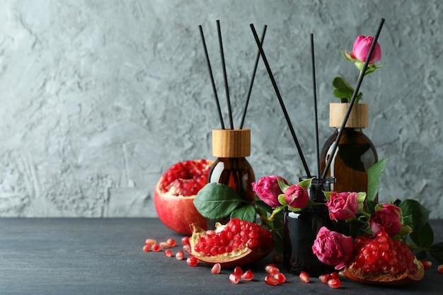 Diffusers, bloemen en granaatappel op donkere houten tafel