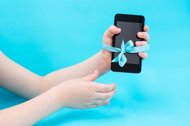 Digitaal detoxconcept. een kinderhand met een smartphone wordt met een blauw lint vastgebonden en een tweede hand reikt naar hen. gadgetverslaving